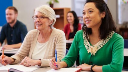 diverse students in a classroom gaze ahead while taking notes