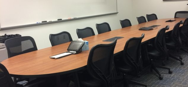 Large central conference room wood table surrounded by black executive office chairs