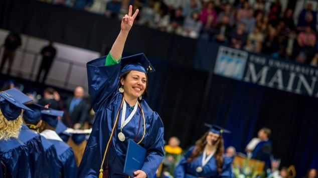 Student in graduation cap and gown throws the victory sign