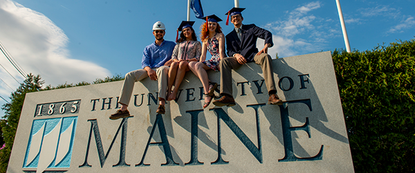 Four students with graduation caps sit on UMaine sign