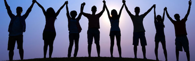 silhouette of eight people holding their hands raised up in front of a sunset
