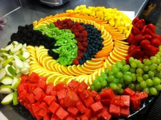 variety platter of fresh fruit slices including watermelon, grapes, strawberries, blueberries, oranges, pineapple