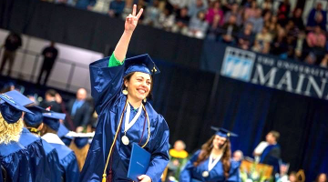 Graduation photo victory pose in blue cap and gown hand raised showing peace sign
