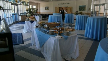 Hutchinson Center Atrium with high top tables covered in light blue table clothes next to rectangular food tables