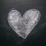 Solid heart drawn in white chalk on black chalkboard