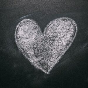 Solid heart drawn in white chalk on black chalkboard