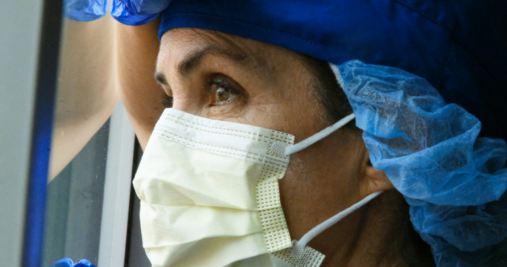 Health care worker wearing mask and looking out a window