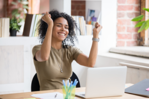 Black woman rejoicing at a laptop