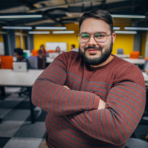 photo of man with beard and glasses in an office setting, looking happy