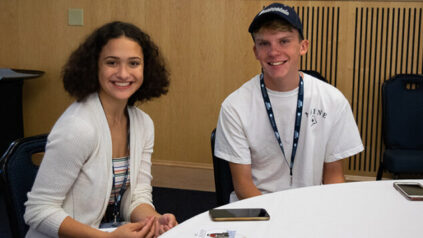 Two UMaine students sit next to each other at orientation