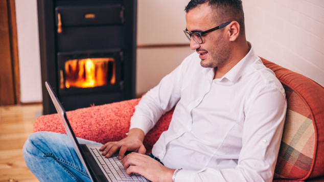 person with laptop in front of wood stove
