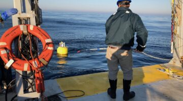 biologist wearing hard hat lowering gear into the water from the stern of a boat