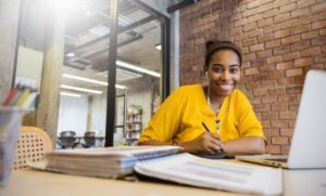 Student with brown skin and yellow t-shirt smiling with pen in hand, studying