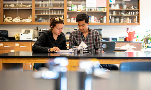 Picture of two students poring over documents in a science classrrom