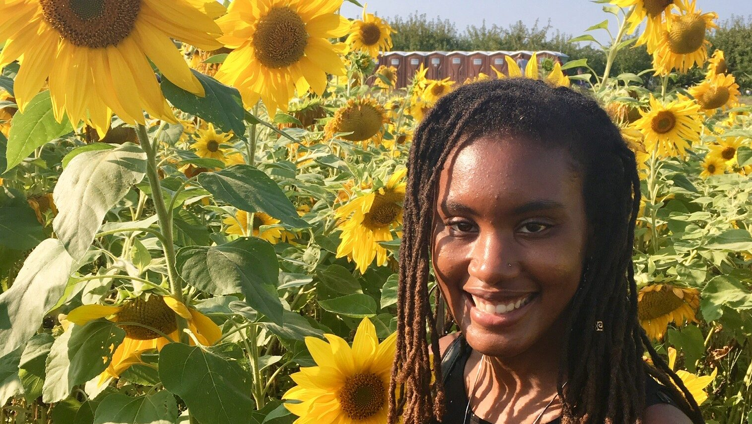 Black woman with dreadlocks standing in a field of sunflowers