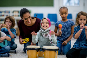 Classroom of students from diverse backgrounds playing musical instruments