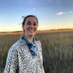 White woman standing in a field at sunset, smiling in to camera