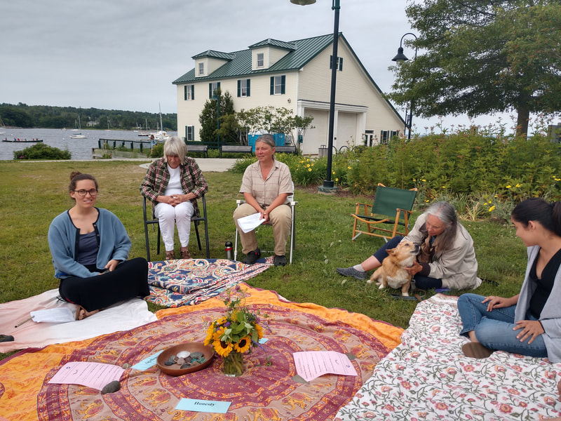 Five people sitting in circle around colorful tablecloth in the park by the bay in Belfast, Maine on a sunny day