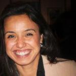 Photo of white woman smiling, dark background