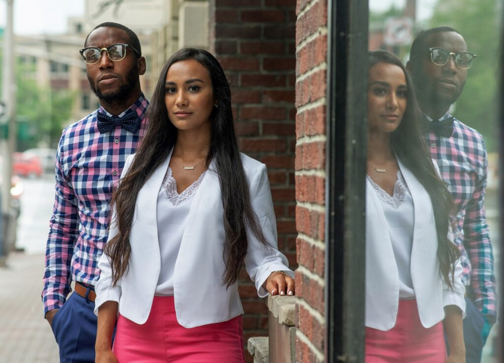 Black man with short hair wearing bow-tie, glasses, and colorful checkered shirt standing behind femme with brown skin and long dark hair wearing white blazer and colorful pants.