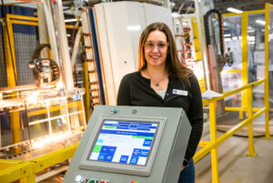 Kristine is a white femme wearing safety glasses behind a machine in a windows making factory