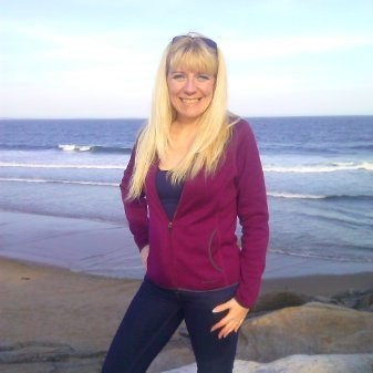 Photo of white femme with long blonde hair in purple cardigan in front of the ocean